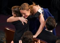 Brie Larson hugs actor Jacob Tremblay before accepting the award for Best Actress in Room at the 88th Oscars.