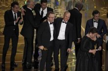 Writer-directo Tom McCarthy is embraced by Michael Keaton as the actors and crew of Spotlight gather on stage to celebrate winning best picture.